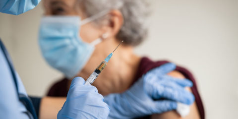 Doctor makes vaccination to senior woman with surgical mask